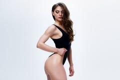 Amincissez le modèle femelle dans une combinaison noire sur le fond blanc Image stock