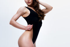 Amincissez le modèle femelle dans une combinaison noire sur le fond blanc Image libre de droits