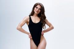 Amincissez le modèle femelle dans une combinaison noire sur le fond blanc Photos libres de droits