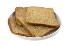 Amincissez le pain coupé en tranches de blé sur le plat Photographie stock