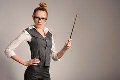 Amincissez le professeur sérieux de jeune femme dans le costume avec l'indicateur à disposition Images stock