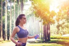 Amincissez le taqueur femelle avec des écouteurs en parc d'été Images libres de droits