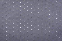 Amincissez le tissu tricoté de couleur lilas grise avec les points blonds Image stock