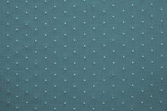 Amincissez le tissu tricoté de couleur verte bleue avec les points blonds Image stock
