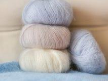 Amincissez les écheveaux pelucheux de la laine pour tricoter un pâle - rose, le bleu et soyez Image libre de droits