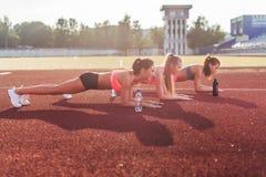 Amincissez les femmes sportives faisant l'exercice de parquet dans le stade Images libres de droits