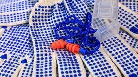 Amincissez les gants de travail avec les boutons bleus et les prises d'oreille sur une surface tournante, banque de vidéos