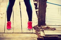 Amincissez les jambes convenables portant les chaussures rouges de sport sur le pilier en bois Photos stock