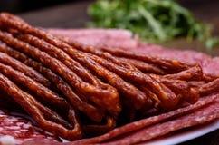 Amincissez les saucisses chaudes et saucisse de découpage en tranches d'un plat Photo libre de droits