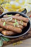 Amincissez les saucisses frites dans une casserole sur un fond en bois Photo stock
