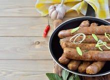 Amincissez les saucisses frites dans une casserole sur un fond en bois Photographie stock