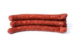Amincissez les saucisses fumées d'isolement sur un fond blanc Images stock