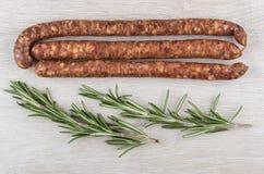 Amincissez les saucisses fumées et les brindilles du romarin sur la table en bois Photos libres de droits
