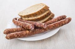 Amincissez les saucisses fumées et les morceaux de pain dans le plat blanc Images stock