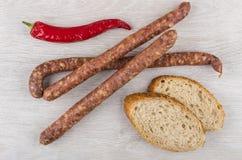 Amincissez les saucisses fumées, le poivre de piment et les morceaux de pain Images stock