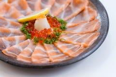 Amincissez Salmon Sashimi Served découpé en tranches avec l'oignon blanc, Ikura Salmon Roe, hachez le radis et le citron coupé en Image stock