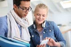 Amis à l'école utilisant le smartphone Images stock
