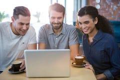 Amis à l'aide d'un ordinateur portable dans le café Photos stock