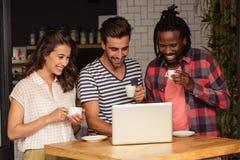Amis à l'aide d'un ordinateur portable et tenant des tasses de café Photos stock