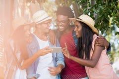 Amis à l'aide d'un téléphone portable Image libre de droits