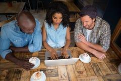 Amis à l'aide de l'ordinateur portable à la table en bois dans le café Image stock