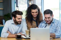 Amis à l'aide de l'ordinateur portable dans le café Photo libre de droits