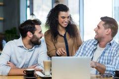 Amis à l'aide de l'ordinateur portable dans le café Photos libres de droits