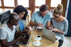 Amis à l'aide de l'ordinateur portable, du téléphone portable et du comprimé numérique tout en ayant le café Photos libres de droits