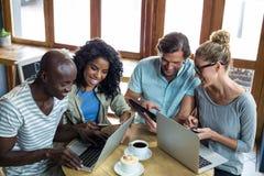 Amis à l'aide de l'ordinateur portable, du téléphone portable et du comprimé numérique tout en ayant le café Image stock