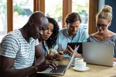 Amis à l'aide de l'ordinateur portable, du téléphone portable et du comprimé numérique tout en ayant le café Images stock