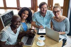 Amis à l'aide de l'ordinateur portable et du comprimé numérique tout en ayant le café dans le café Photo stock