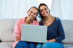Amis à l'aide de l'ordinateur portable sur le sofa Image stock
