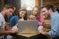 Amis à l'aide de l'ordinateur portable tout en ayant le café Photos stock