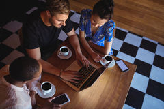 Amis à l'aide de l'ordinateur portable tout en ayant le café Images stock