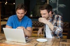 Amis à l'aide de l'ordinateur portable tout en se reposant à la table dans le restaurant Photographie stock libre de droits