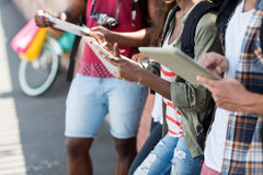 Amis à l'aide de la table numérique et du téléphone portable Photo libre de droits