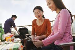 Amis à l'aide de la Tablette de Digital au barbecue de dessus de toit Photos stock