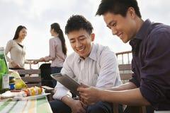 Amis à l'aide de la Tablette de Digital au barbecue de dessus de toit Photographie stock libre de droits