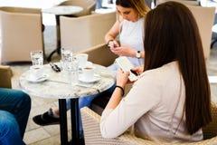 Amis à l'aide de leurs téléphones portables et s'ignorant tout en se reposant au café Photo stock