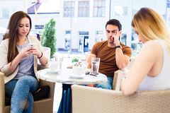 Amis à l'aide de leurs téléphones portables et s'ignorant tout en se reposant au café Image stock