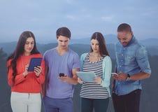 Amis à l'aide des comprimés numériques et du téléphone portable en atmosphère d'obscurité Image libre de droits