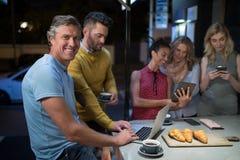 Amis à l'aide des instruments électroniques tout en ayant le café Image libre de droits