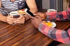 Amis à l'aide des smartphones Photos stock