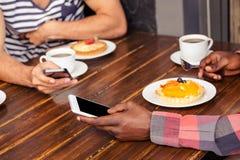 Amis à l'aide des smartphones Photos libres de droits