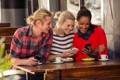 Amis à l'aide des smartphones Photographie stock libre de droits