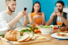 Amis à l'aide des smartphones à la table complètement de la nourriture images stock