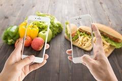 Amis à l'aide des smartphones pour prendre des photos avec la nourriture contrastante Photographie stock