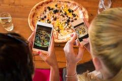Amis à l'aide des smartphones pour prendre des photos de leur pizza Photo libre de droits