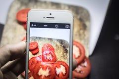 Amis à l'aide des smartphones pour prendre des photos de nourriture Images stock