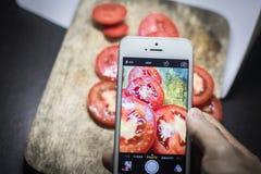 Amis à l'aide des smartphones pour prendre des photos de nourriture Photo libre de droits
